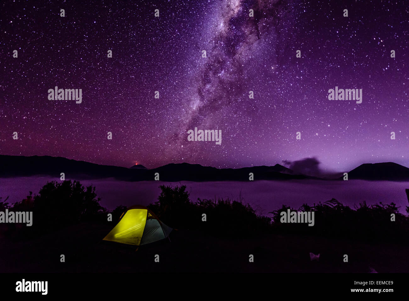 Milky Way galaxy over campsite in starry night sky - Stock Image