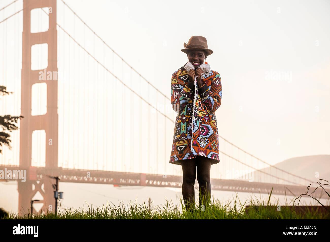 Black woman wearing colorful coat by Golden Gate Bridge, San Francisco, California, United States Stock Photo