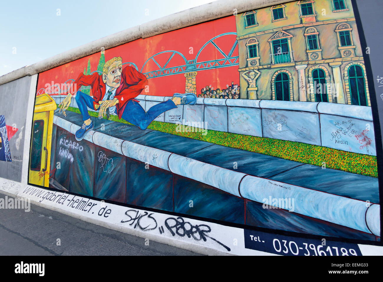 Germany, Berlin: Wall painting of a man jumping the wall to escape east Germany at East Side Gallery - Stock Image