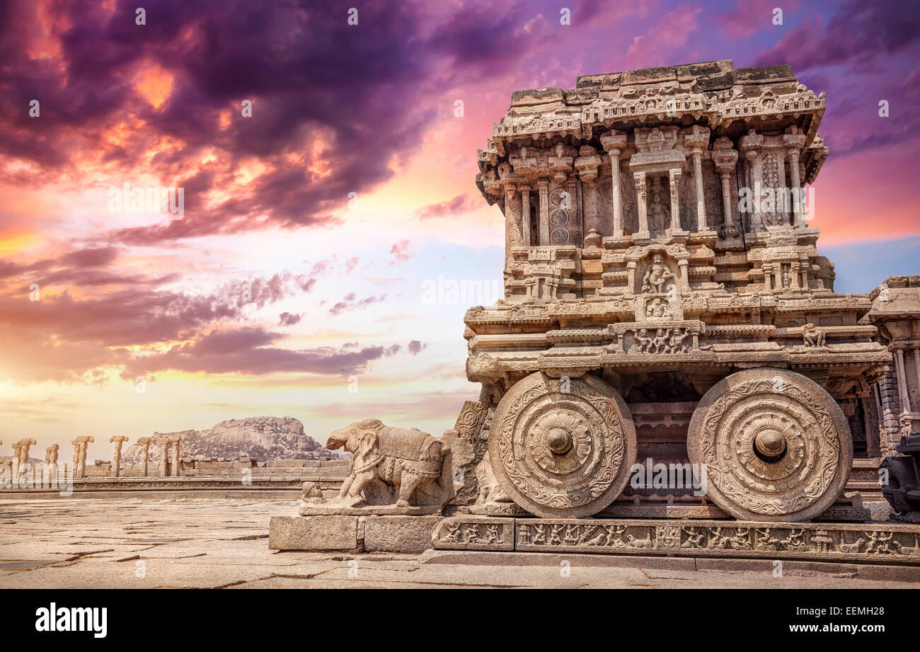 Stone chariot in courtyard of Vittala Temple at sunset purple sky in Hampi, Karnataka, India - Stock Image