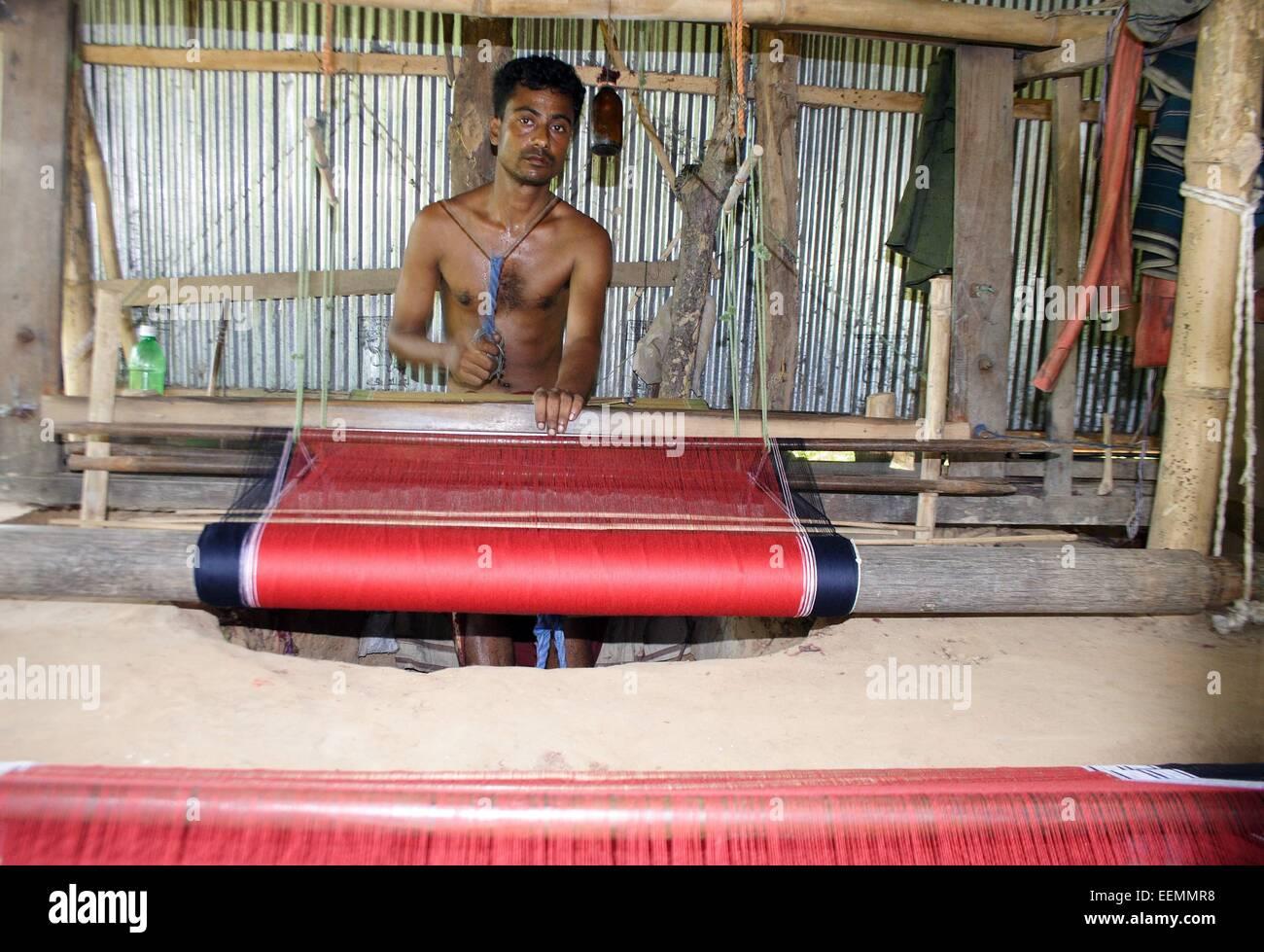Bangladesh 10 January 2015. A Tribal man weaving cloth on an old traditional loom. - Stock Image
