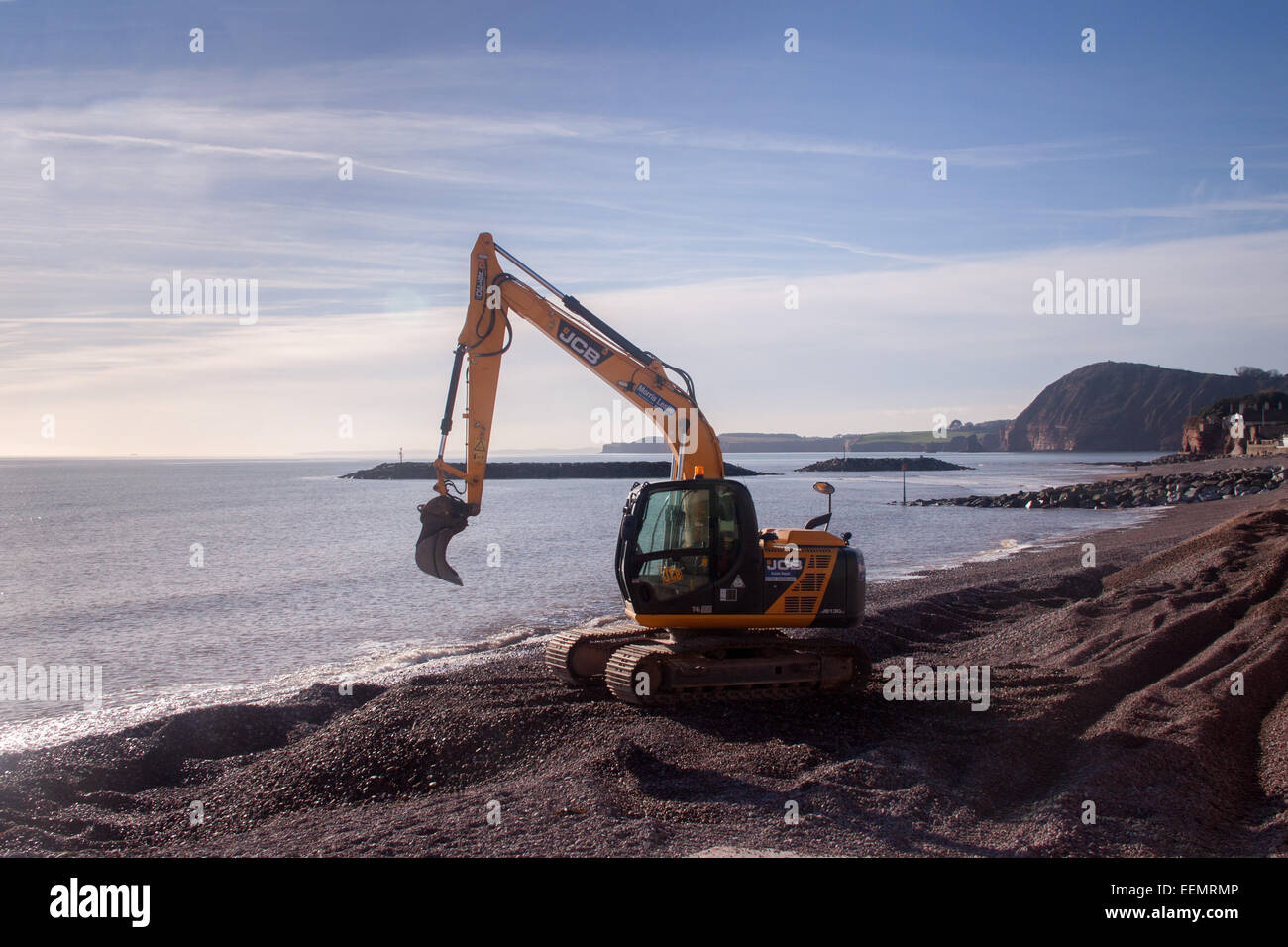 A JCB digger moves shingle on the beach at Sidmouth, Devon. - Stock Image
