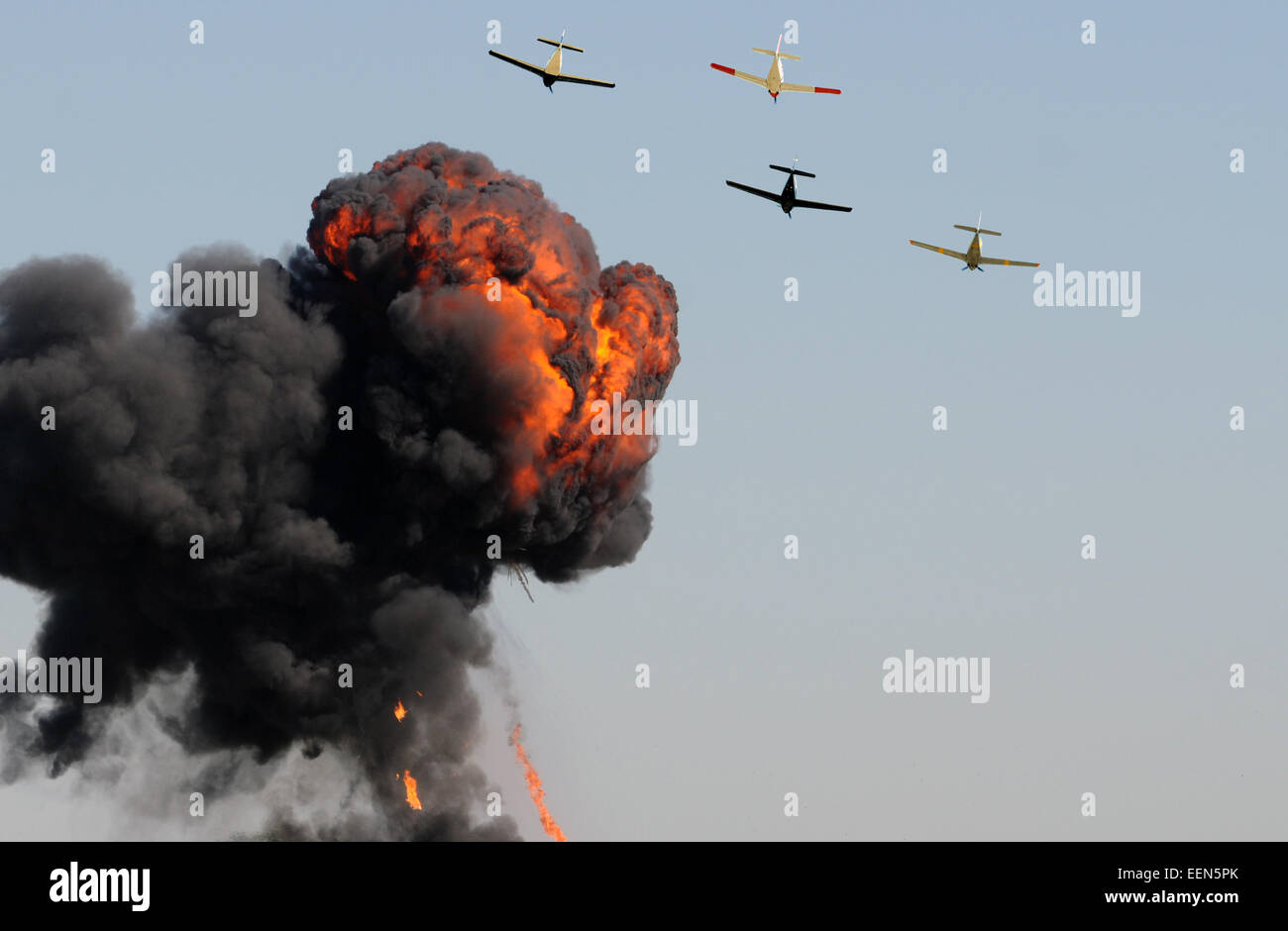 Old airplanes in a bombing run with smoke and fire - Stock Image