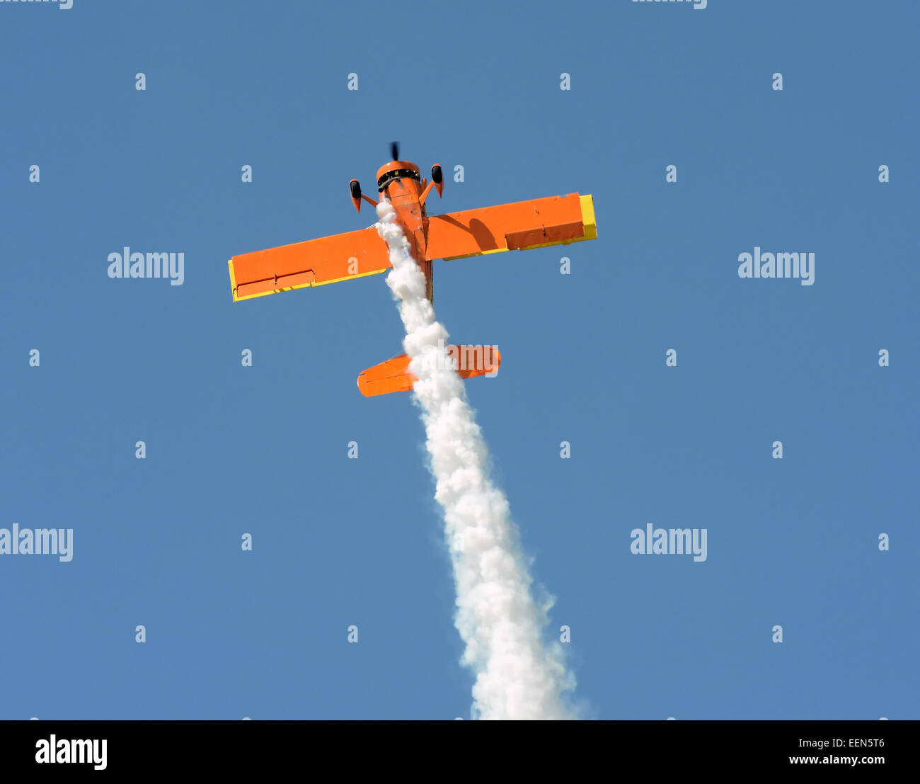 retro orange colored airplane performing aerobatics - Stock Image