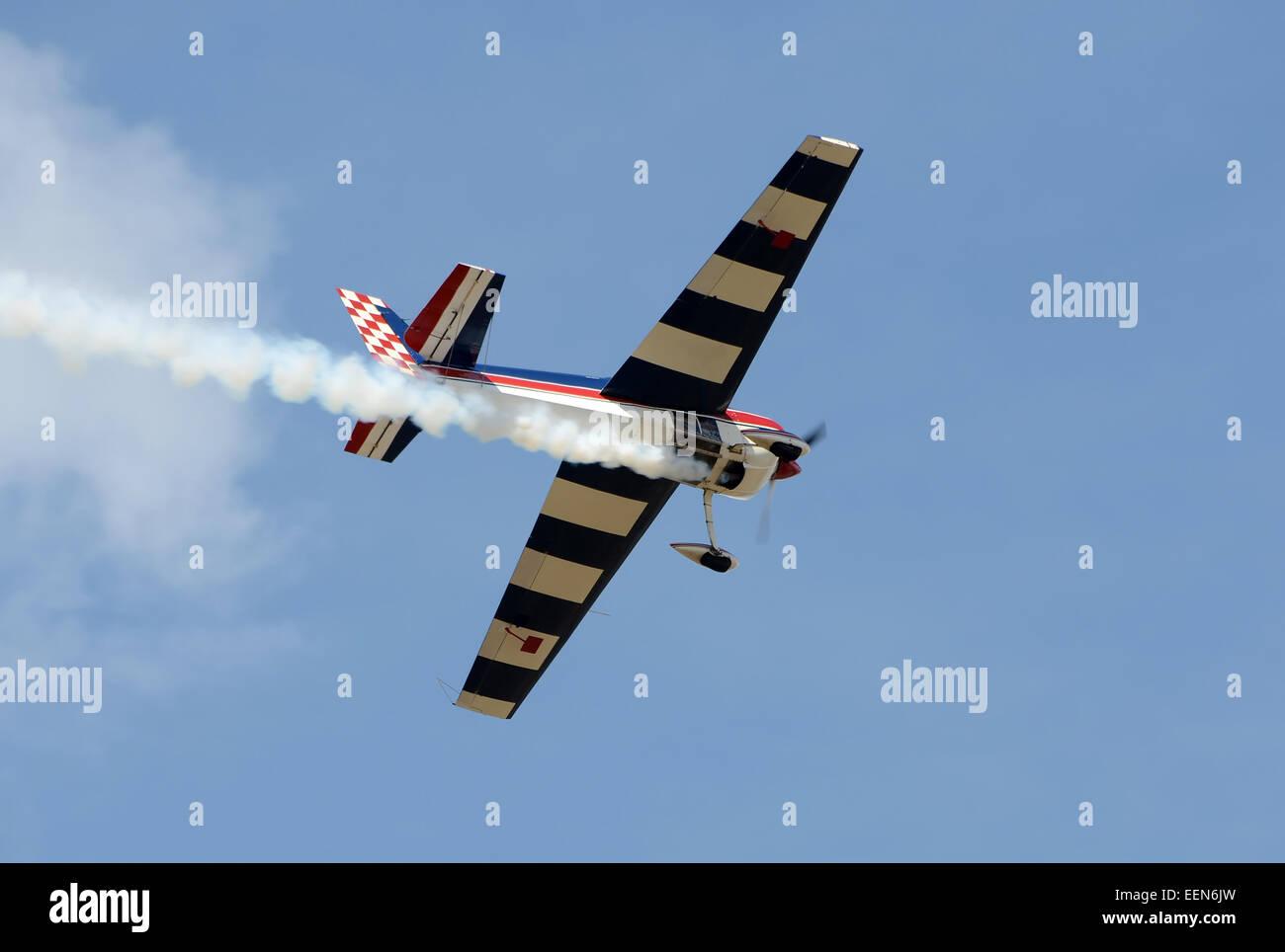 Light aerobatic airplane practicing maneuvers - Stock Image
