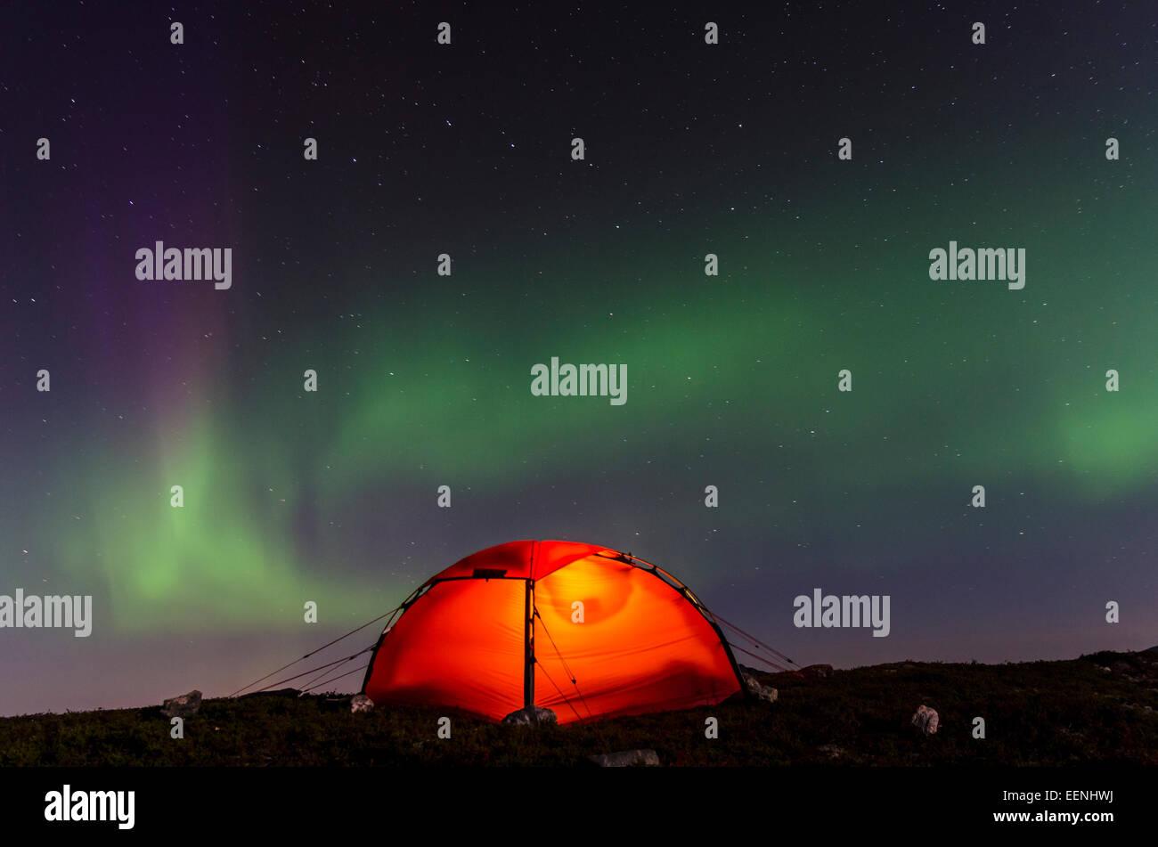 Nordlicht (Aurora borealis) ueber einem erleuchteten Zelt, Moere und Romsdal Fylke,  Vestland, Norwegen, September - Stock Image