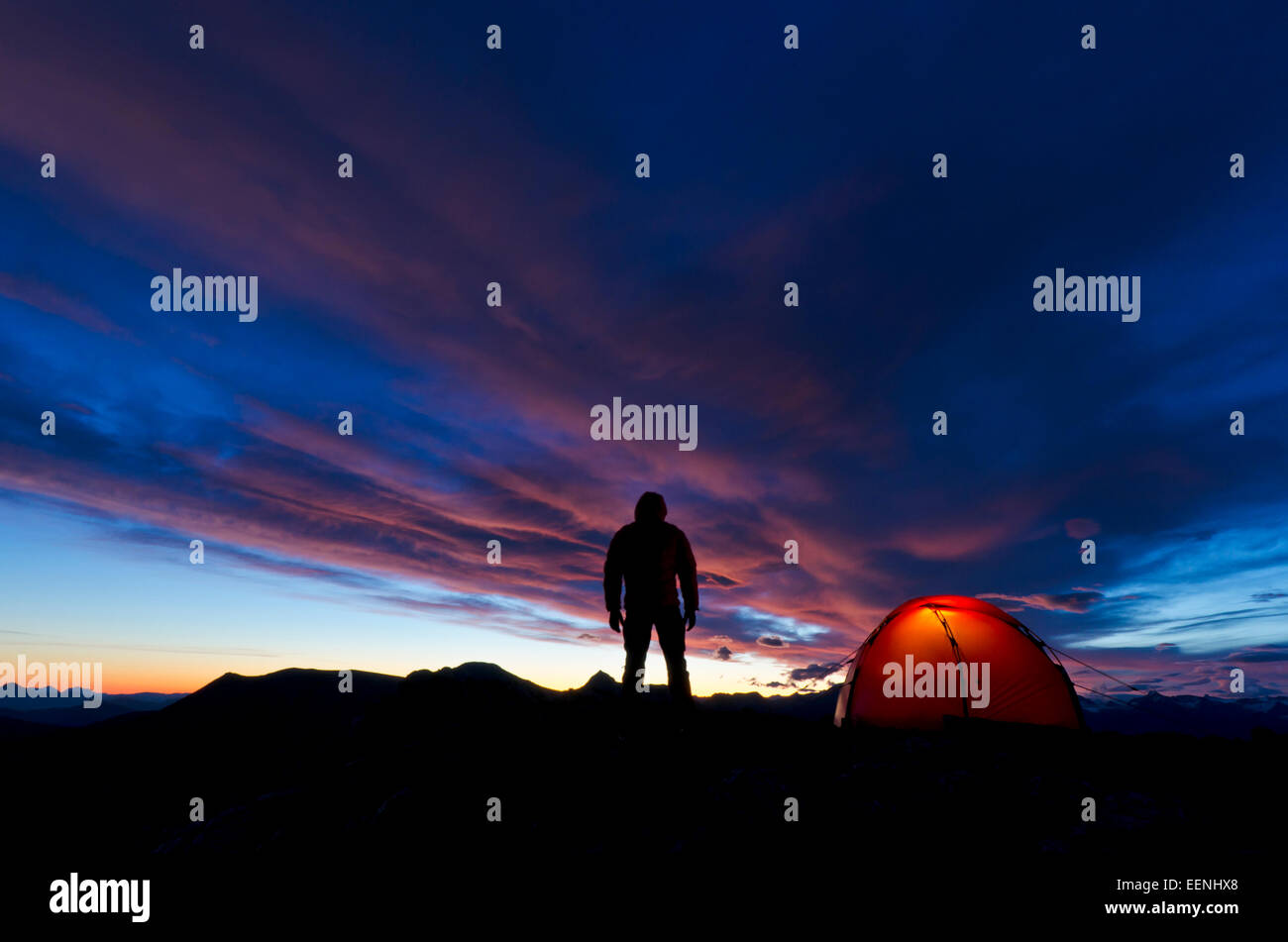 Man stands in the dawn -lit next to his tent, Moere und Romsdal Fylke, Vestland,  Norway, September - Stock Image