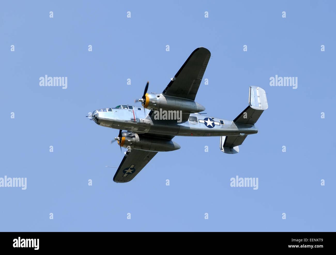 World War II era bomber flying against blue sky B-25 Mitchell Stock Photo