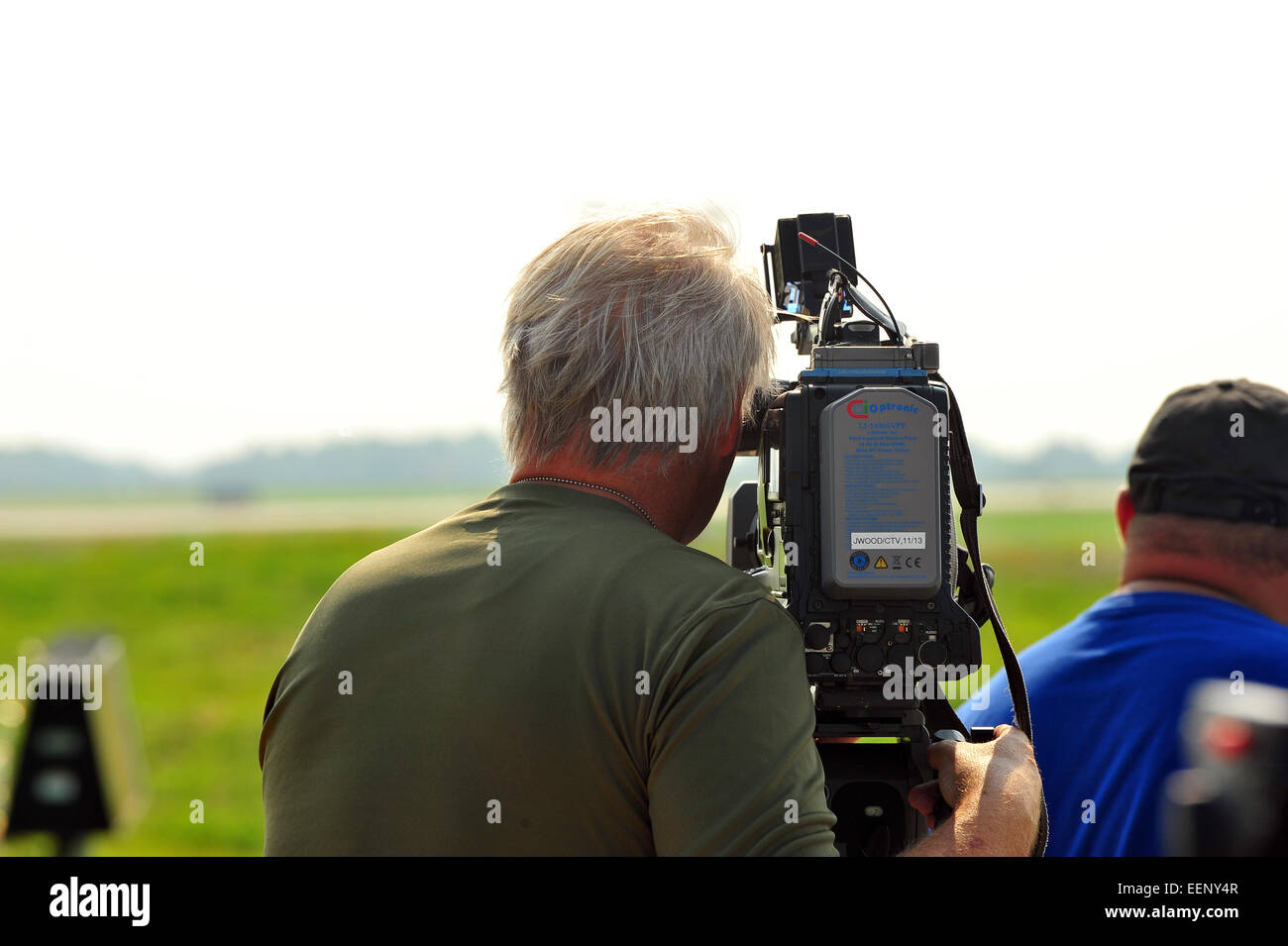 The back of a cameraman filming at an airport. - Stock Image