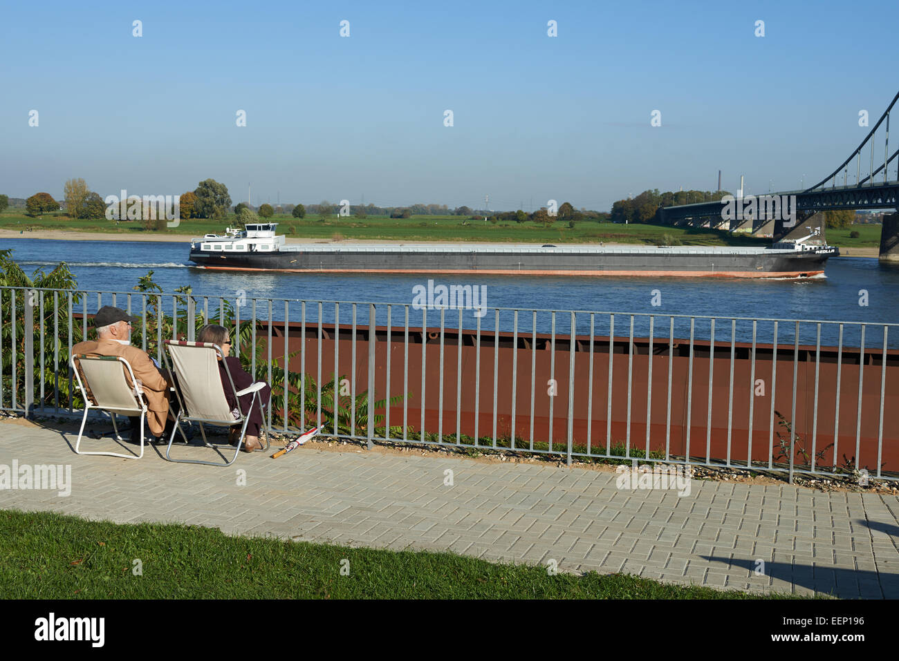 Elderly couple sitting on the banks of the river Rhine, Krefeld, Germany. - Stock Image