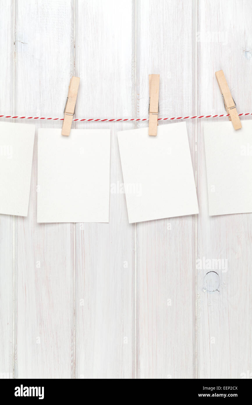 Photo frames hanging on rope over white wooden background Stock ...