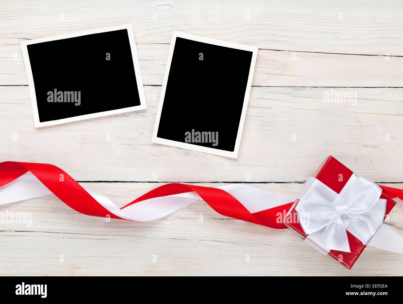 Photo frame cards and gift box with ribbon over wooden table background - Stock Image