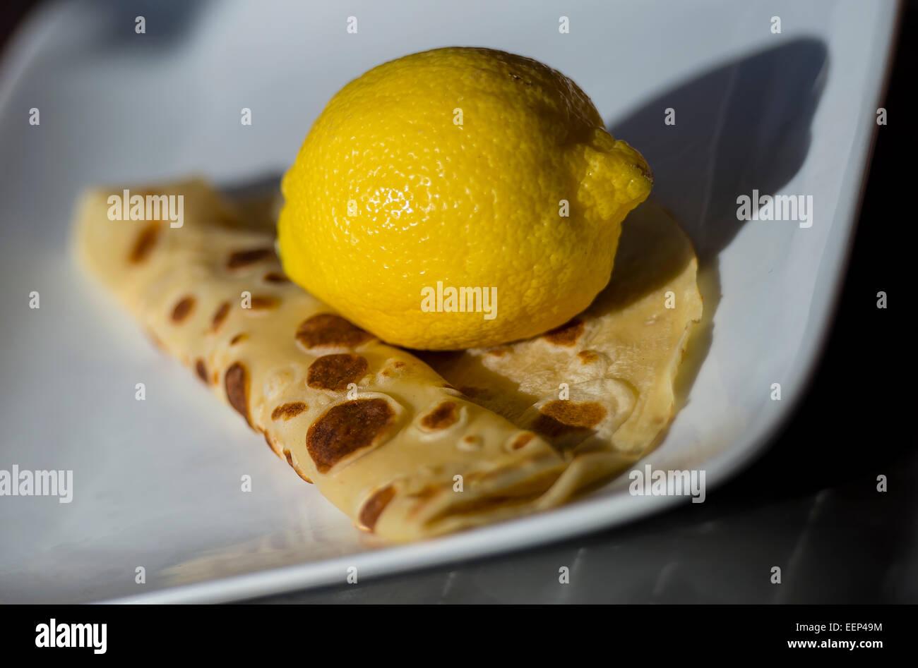 Pancake on a plate with a lemon. A popular pancake is lemon and sugar - Stock Image