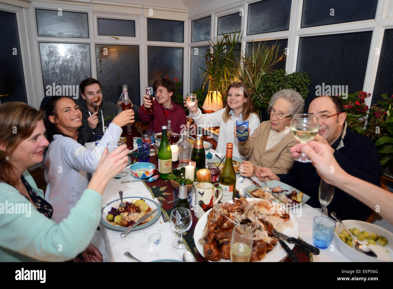 Family enjoy Christmas dinner with all the generations. - Stock Image