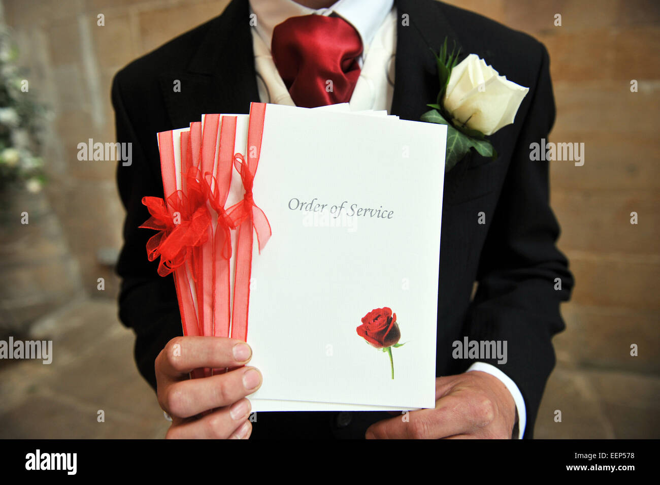 Close up of a best man with the order of service before the wedding. - Stock Image