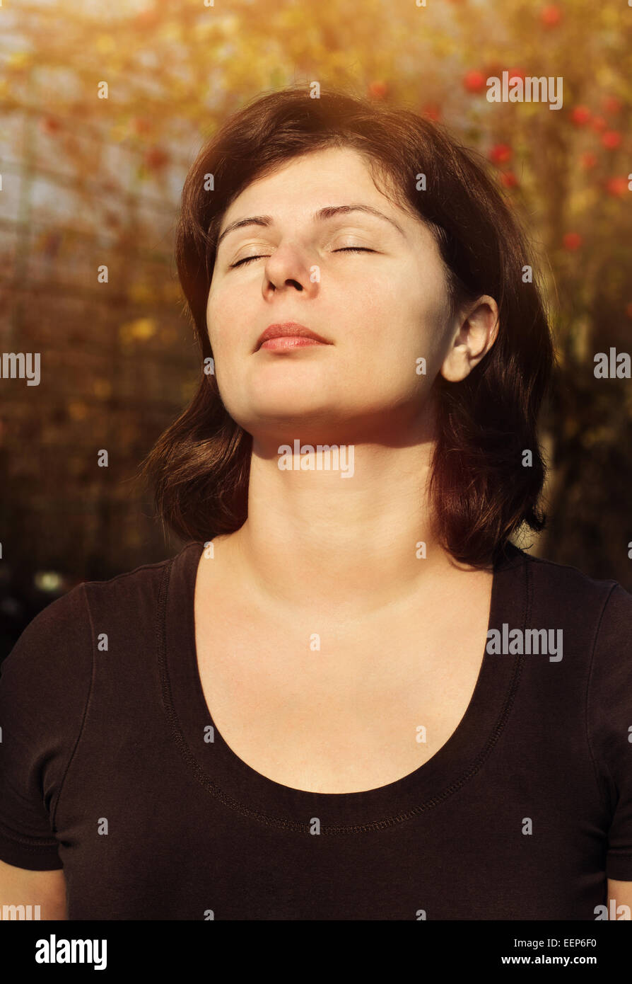 Close up portrait of beautiful woman is smiling with closed eyes over sunlight, meditation outdoor - Stock Image