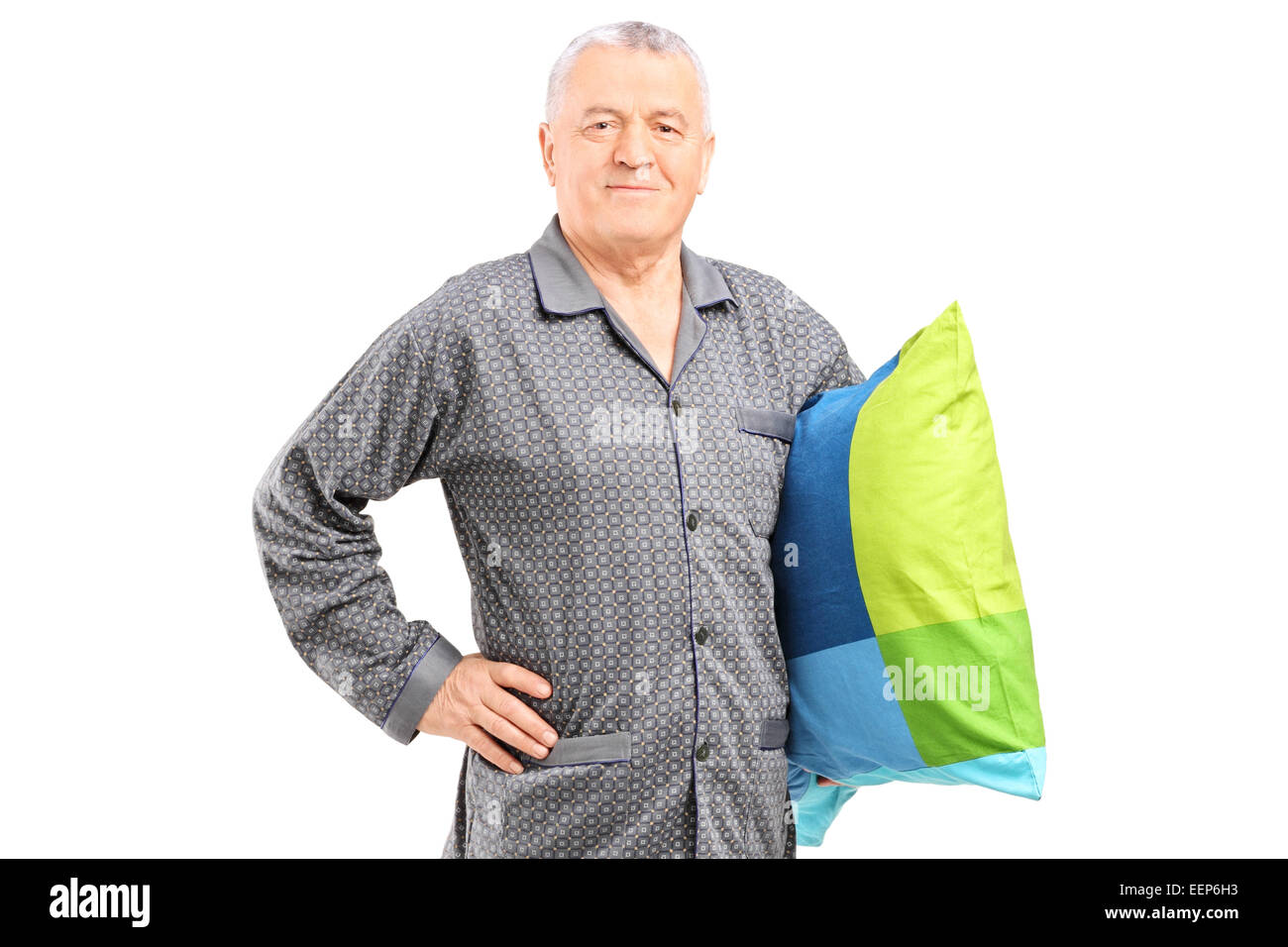 Senior in nightwear holding a pillow isolated on white background - Stock Image