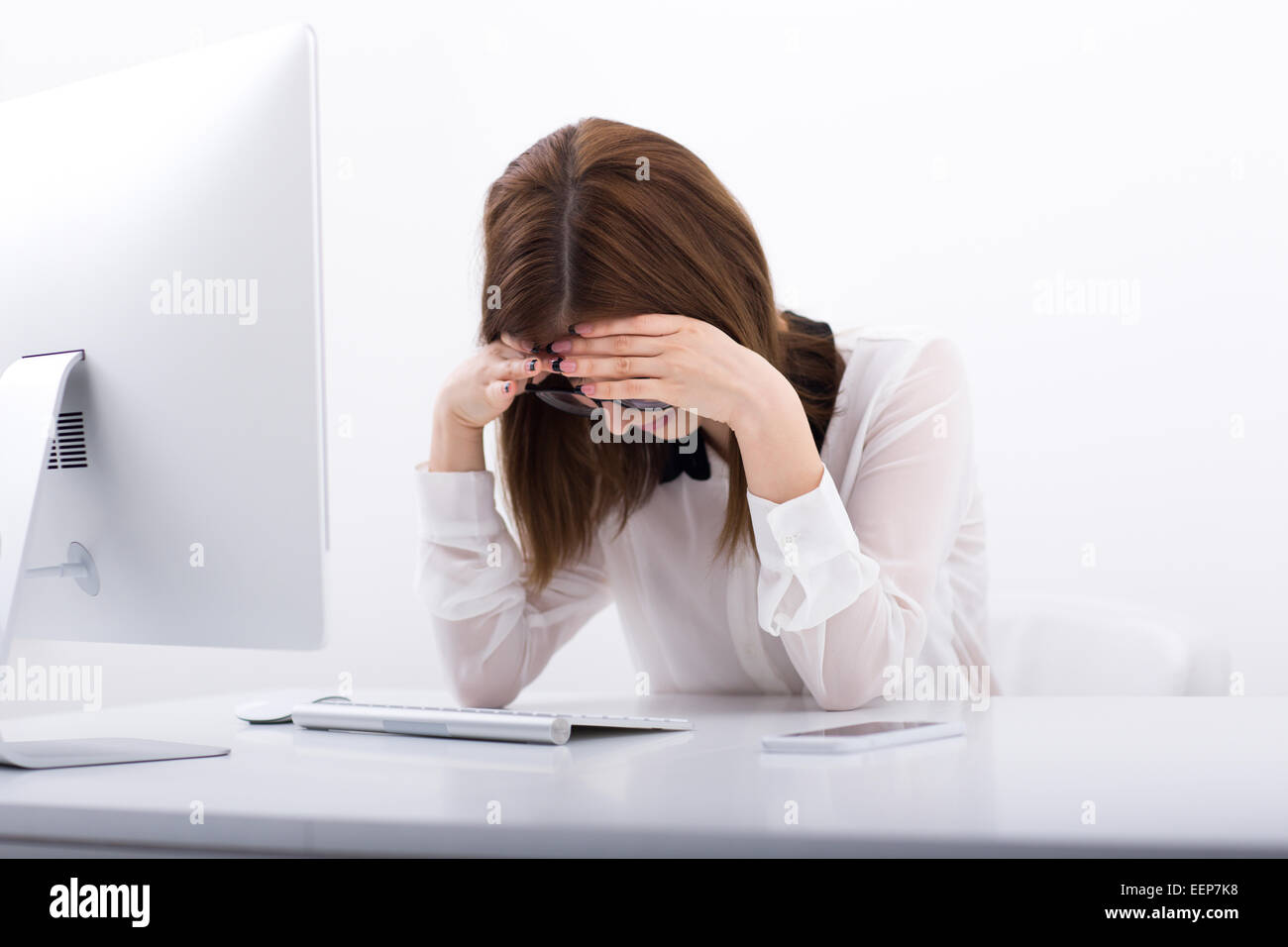 Tired business woman sitting at her workplace in office - Stock Image