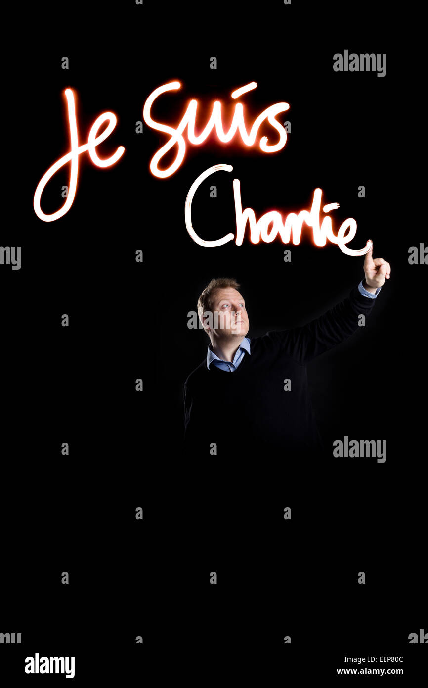 A man writing Je suis Charlie with light. - Stock Image