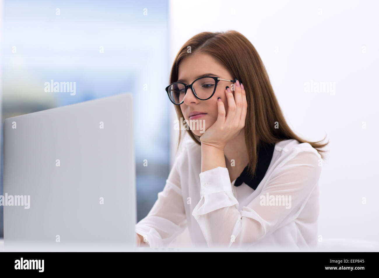 Beautiful businesswoman working on the laptop at office - Stock Image