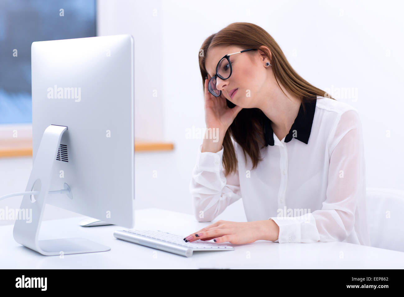 Tired businesswoman working in office - Stock Image