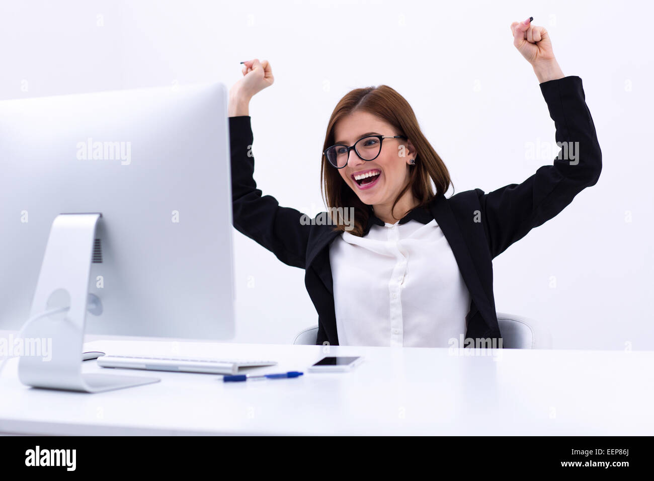 Excited businesswoman rejoicing at her success cheering and raising her fists in the air - Stock Image