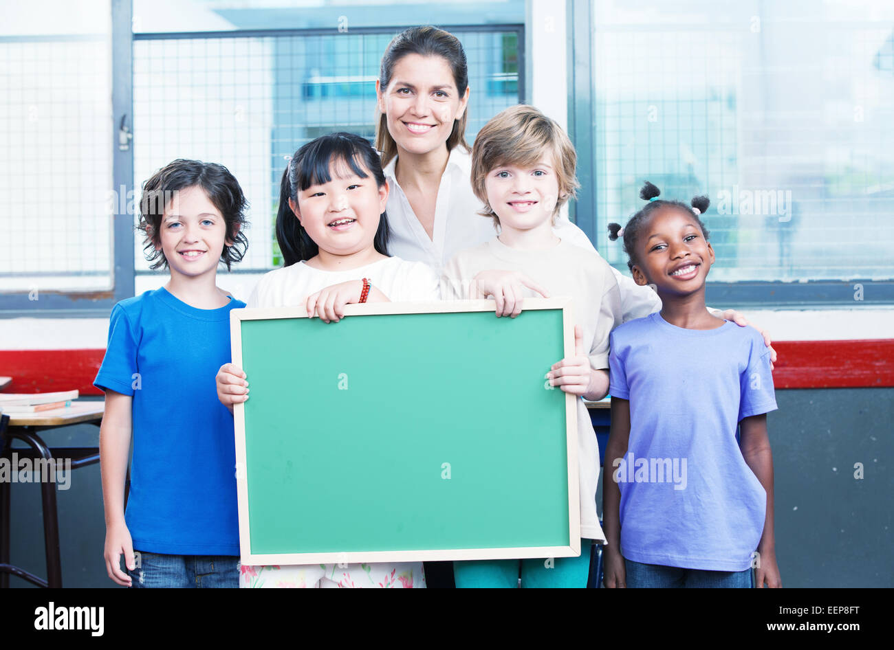 Happy students and teacher  holding empty chalkboard. Primary school interracial concept. Stock Photo