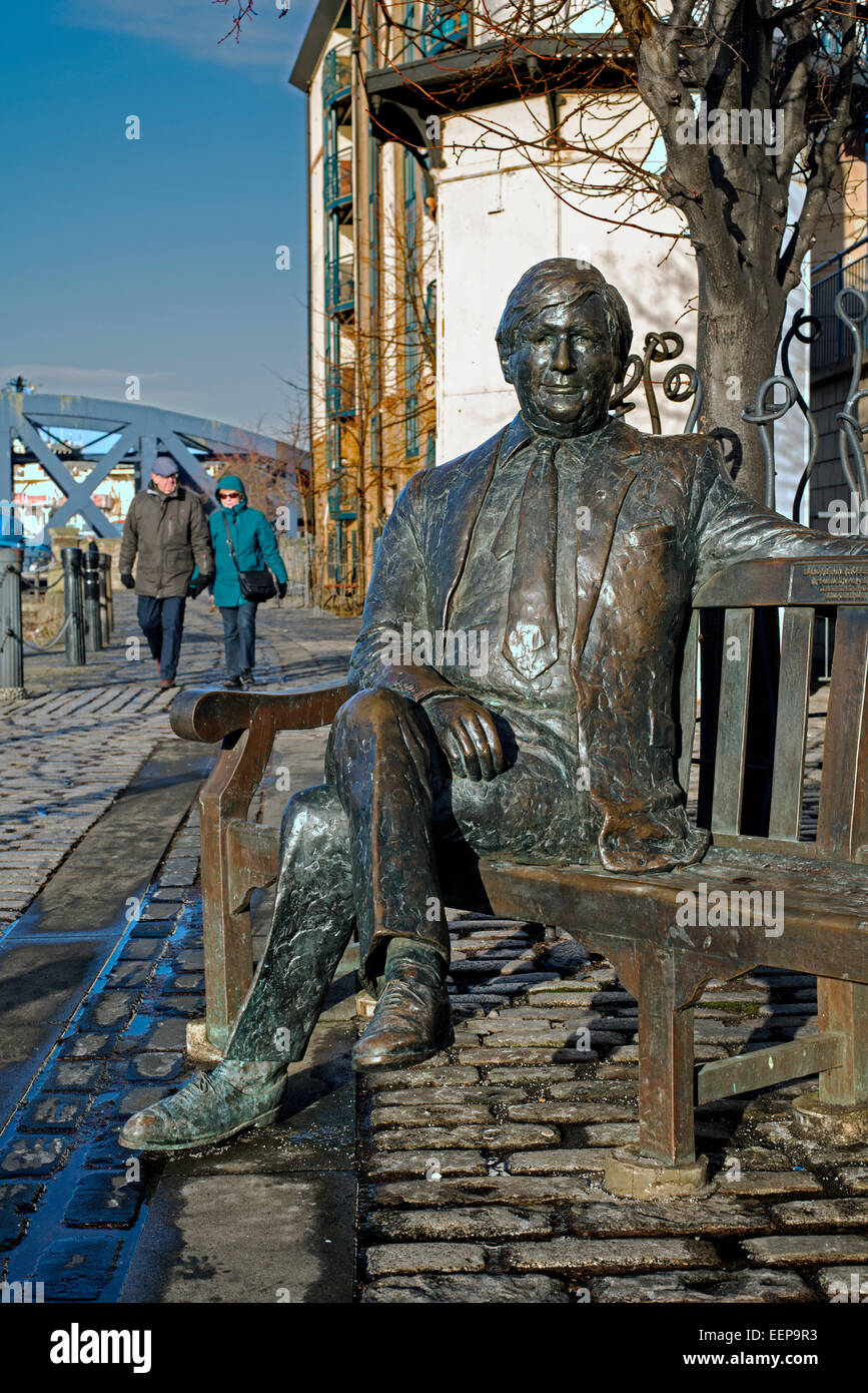 Life-size bronze sculpture of Sandy Irvine Robertson OBE (1942-1999) , sitting on a bench at the Shore, Leith, Edinburgh. - Stock Image