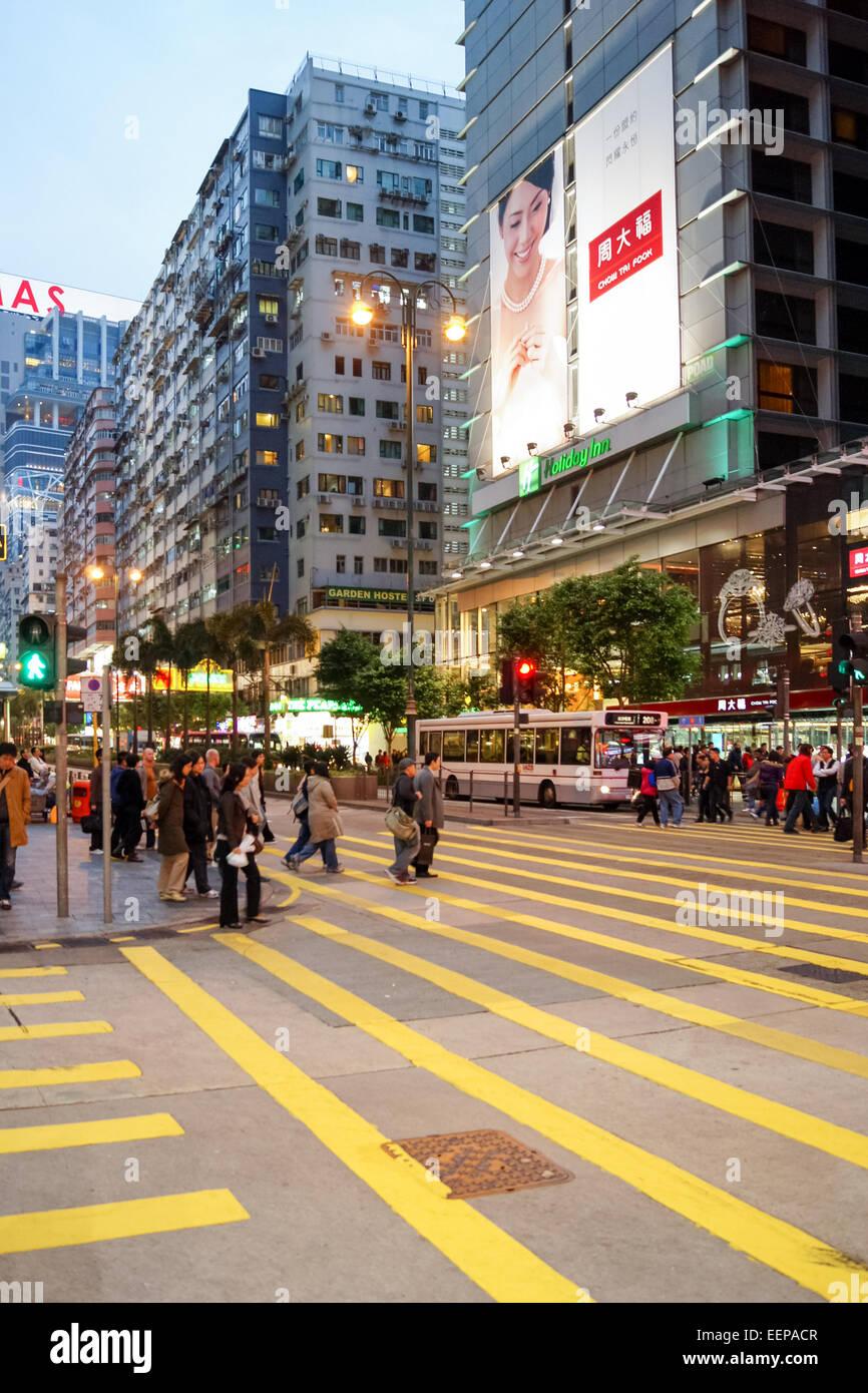 Painted yellow lines at a crossing and junction in Tsim Sha Tsui, Kowloon, Hong Kong, China - Stock Image