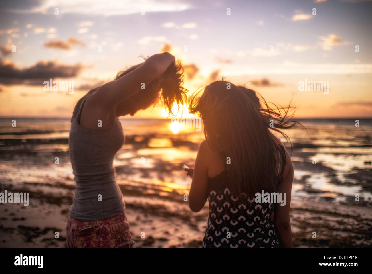 girls tying the hair in the beach - Stock Image