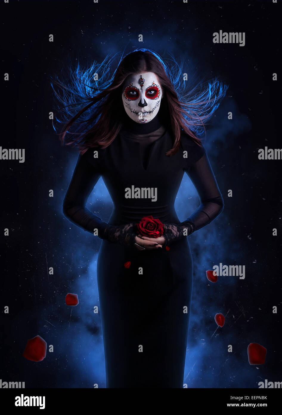 Woman in black dress with sugar skull makeup holding red rose with falling petals at dark background - Stock Image