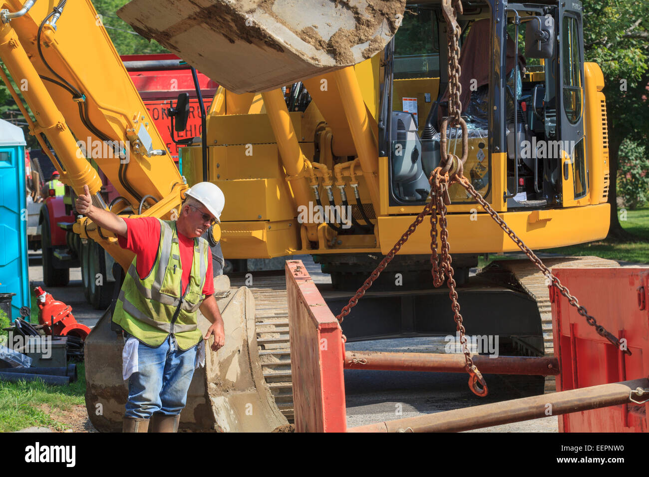 Construction foreman guiding placement of shoring into hole - Stock Image