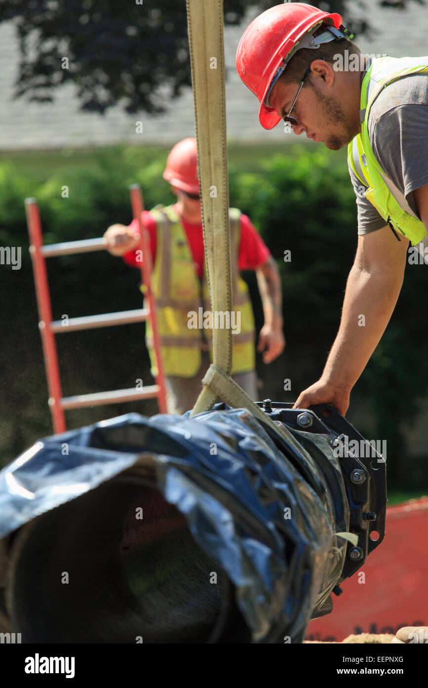 Construction worker using strap on excavator to guide water main section - Stock Image