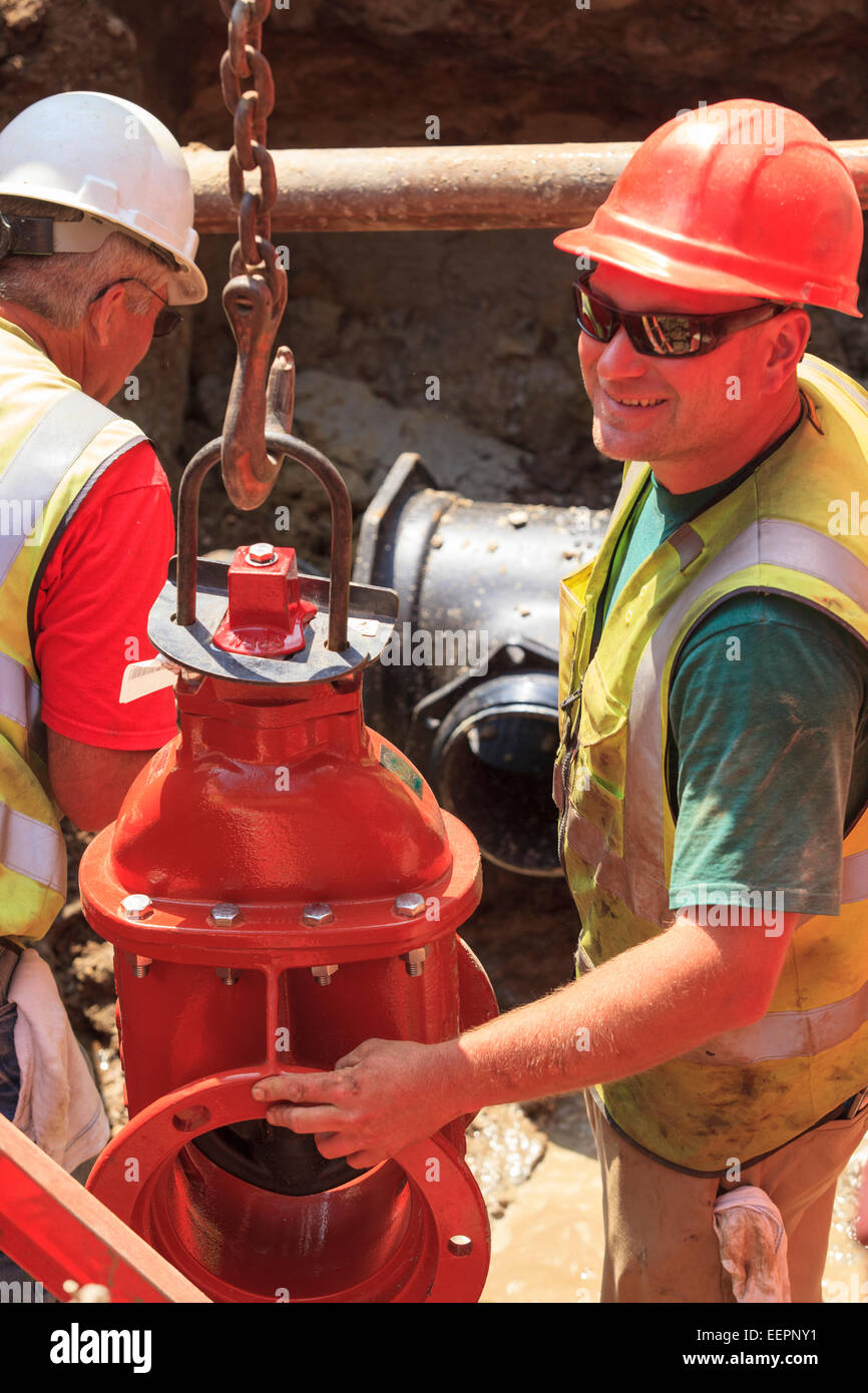 Construction workers preparing to lift gate valve for water main - Stock Image