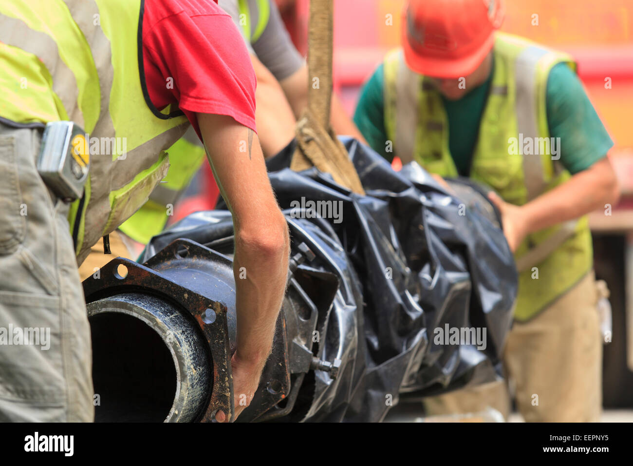 Construction workers guiding water main into place - Stock Image