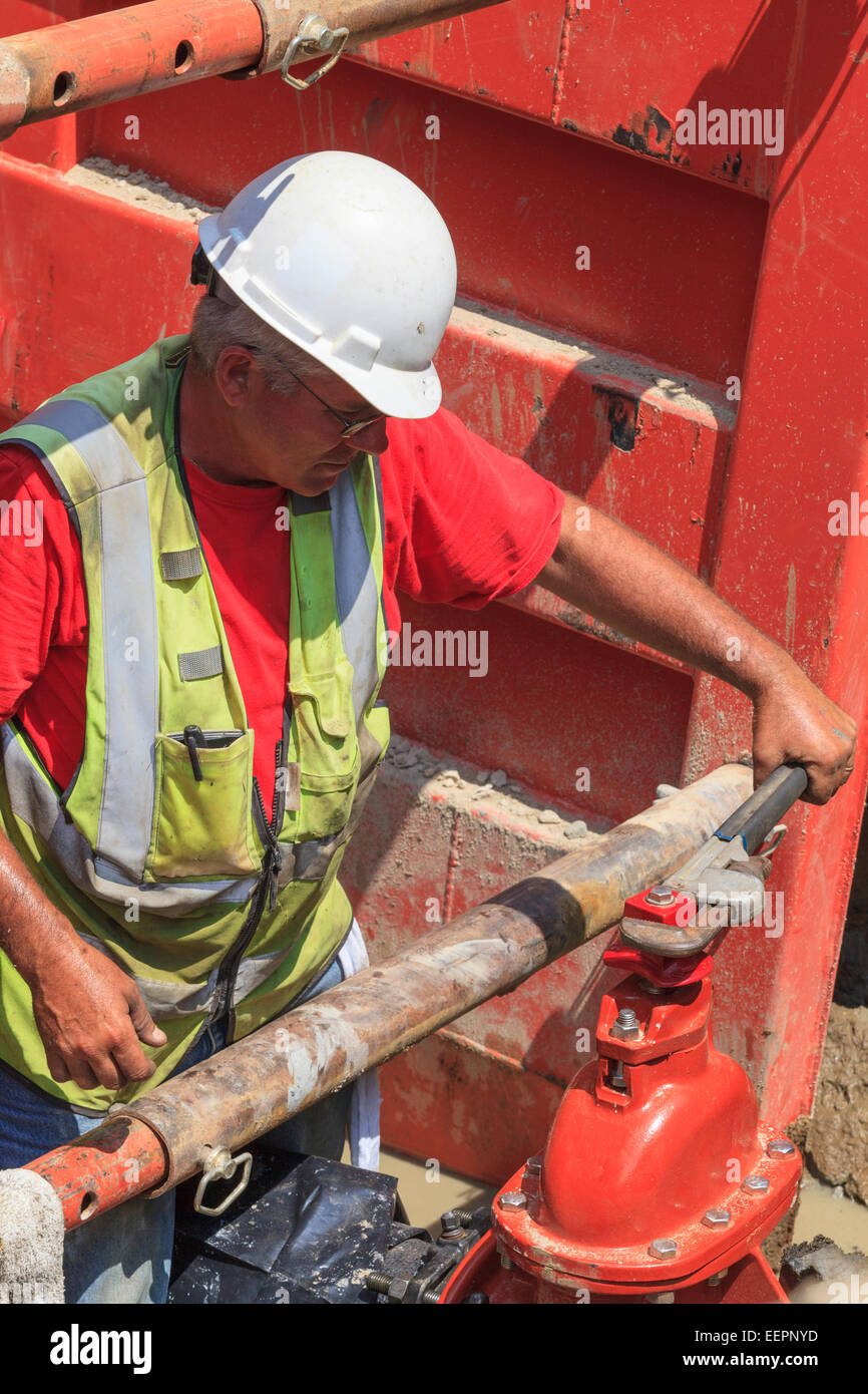 Construction worker using wrench to open gate valve - Stock Image