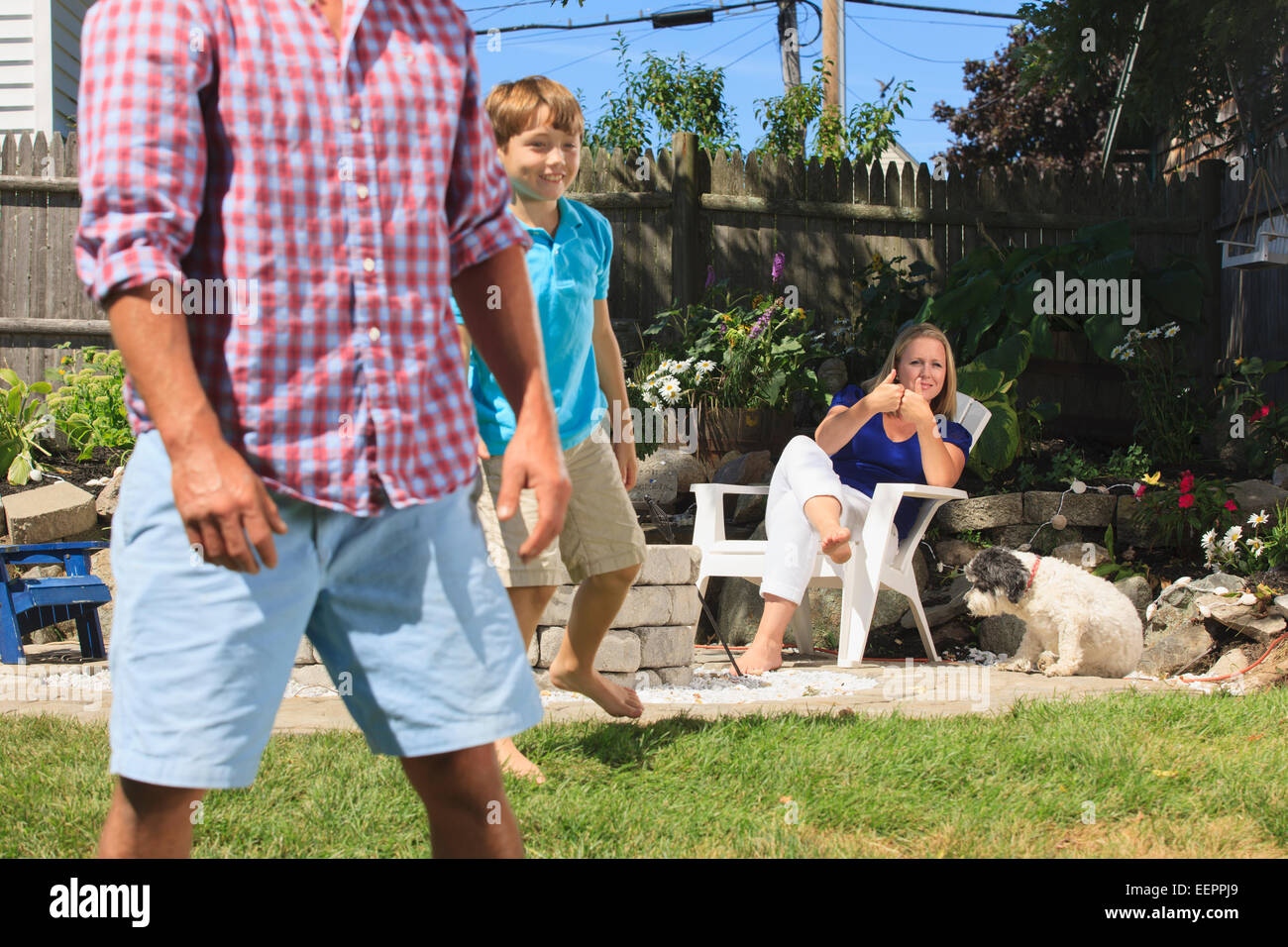 Family with hearing impairments playing football and signing in American sign language in backyard - Stock Image