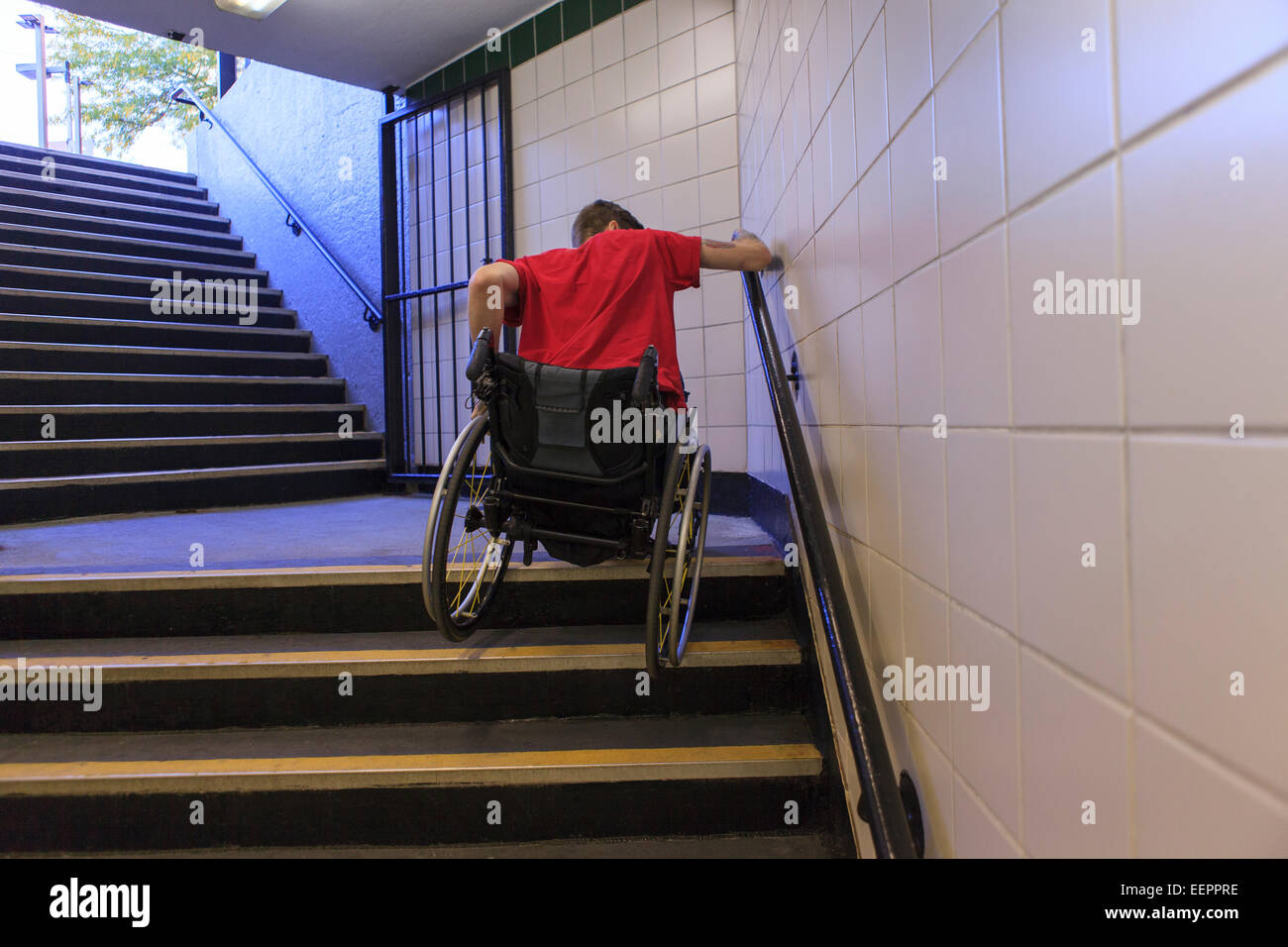 Trendy man with a spinal cord injury in wheelchair going down subway stairs backwards - Stock Image