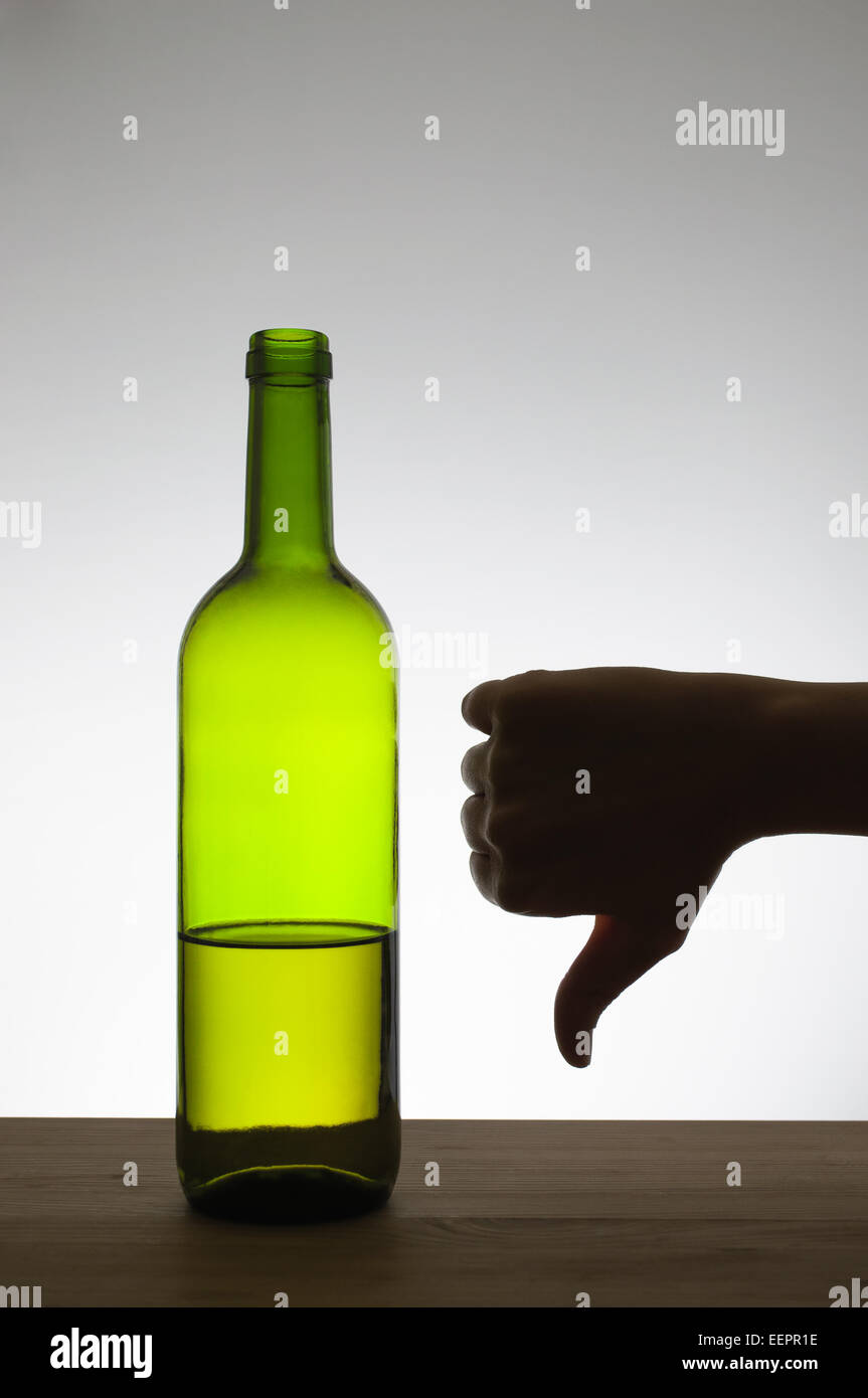 Silhouette of a hand showing thumbs down gesture next to a bottle of wine - Stock Image
