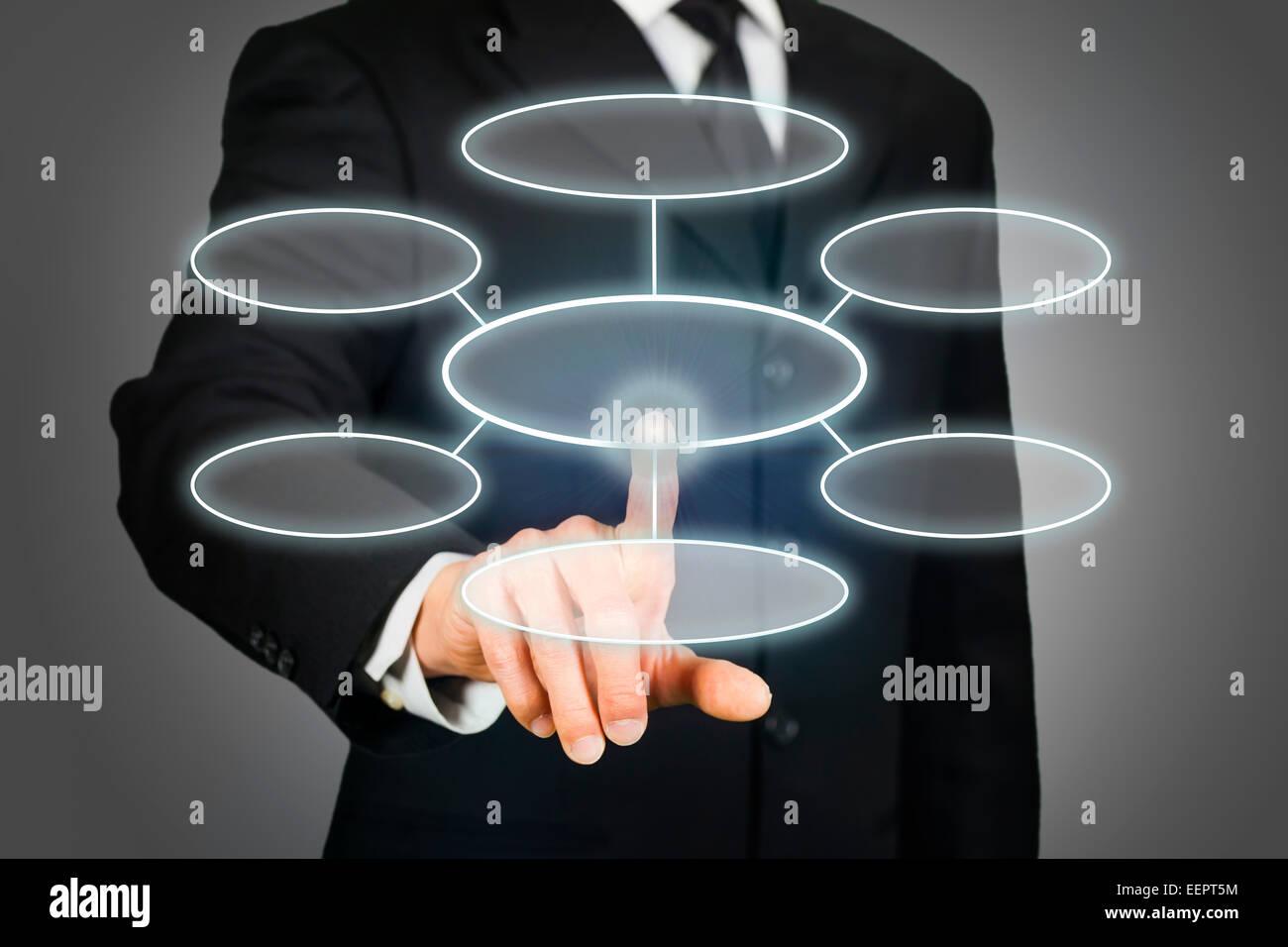 Businessman clicking flowchart on touchscreen - Stock Image