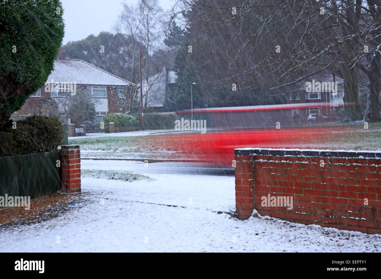A snow shower with motion blur of car on urban road in Hellesdon, Norfolk, England, United Kingdom. - Stock Image