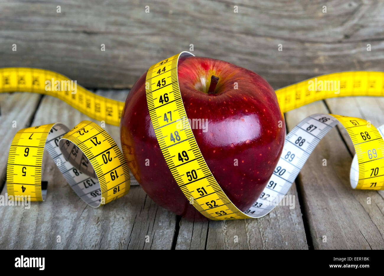 Measuring tape wrapped around a apple weight loss photo - Stock Image