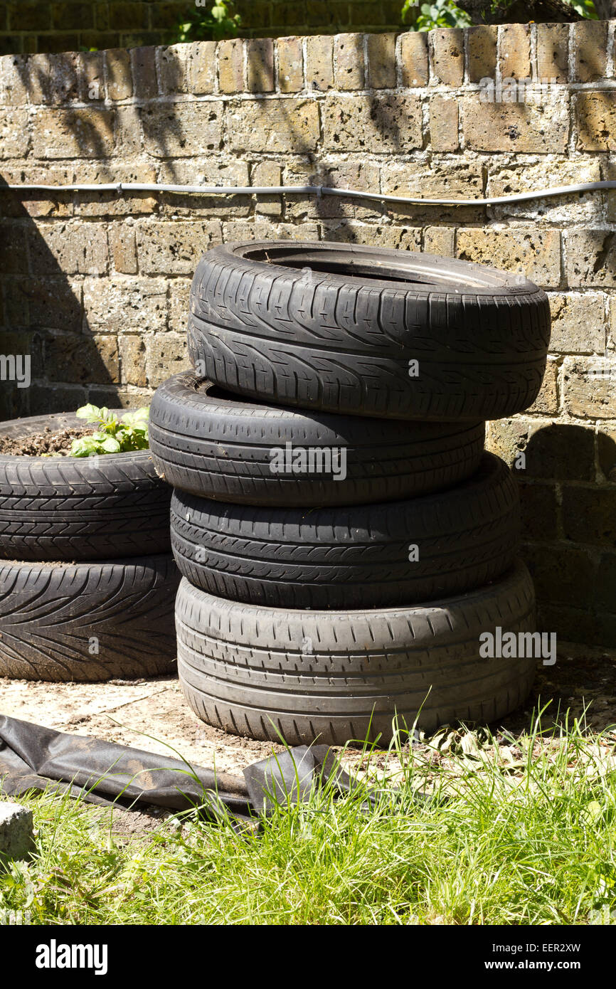 Stack of used tyres being reused as a potato planter - Stock Image