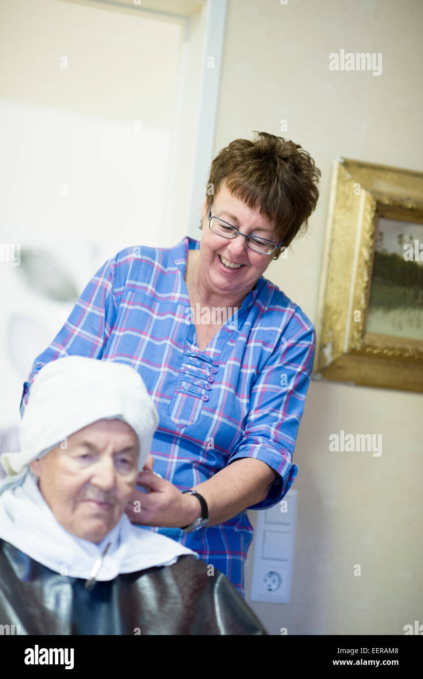 Nursery home, staff helping with hair - Stock Image