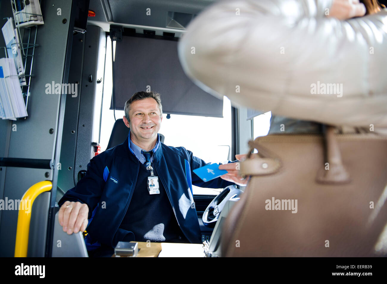 smiling bus driver with passenger - Stock Image