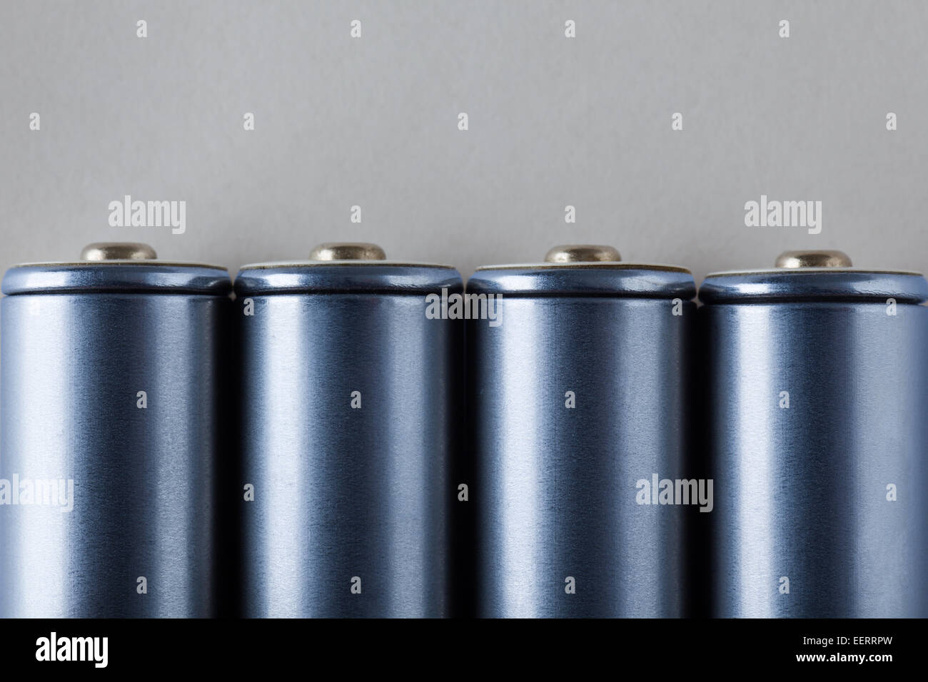 Four AA Blue Batteries on Gray Background - Stock Image