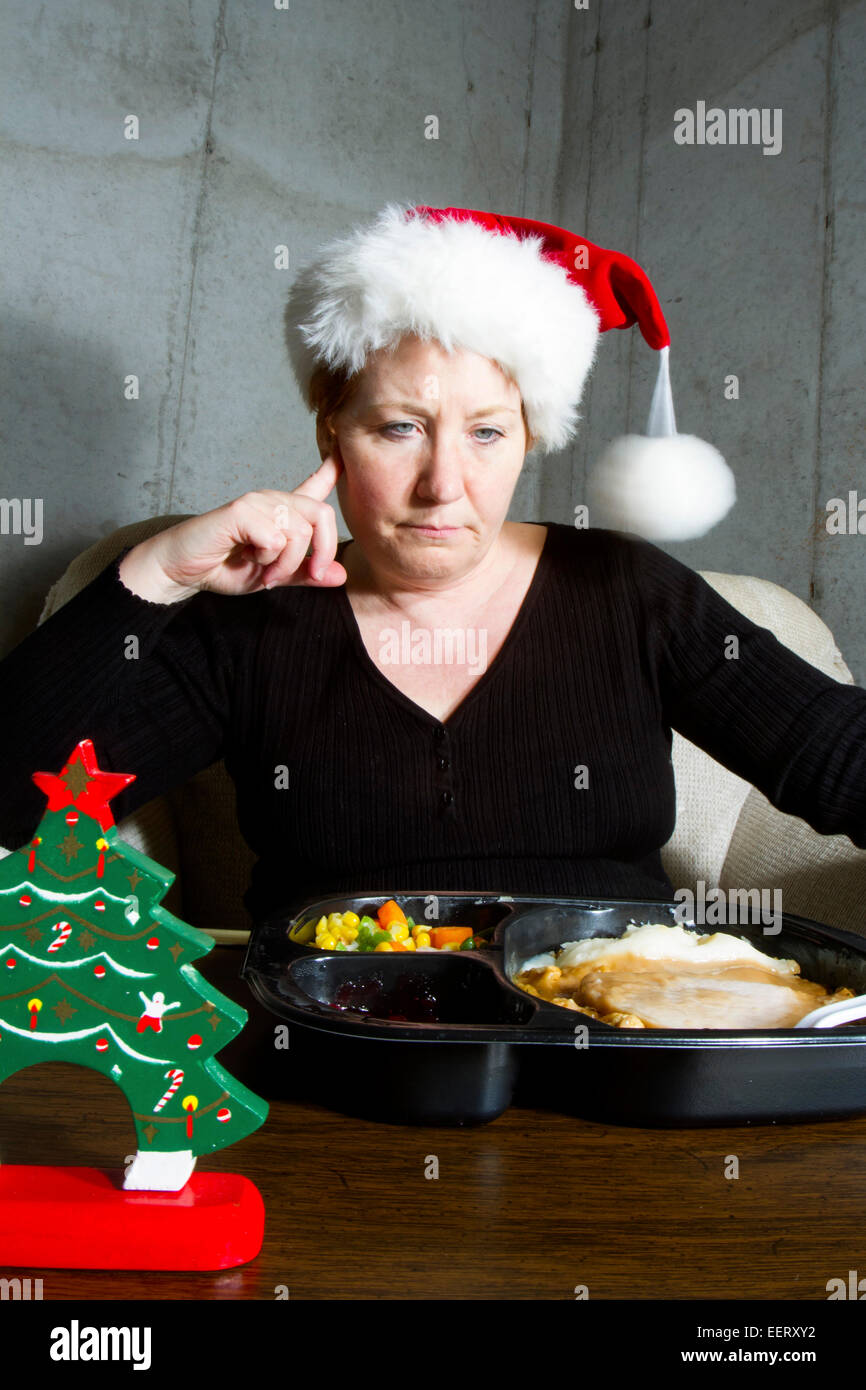 Unhappy woman wearing a christmas stocking hat eating a turkey TV dinner on a tray table in the basement Stock Photo
