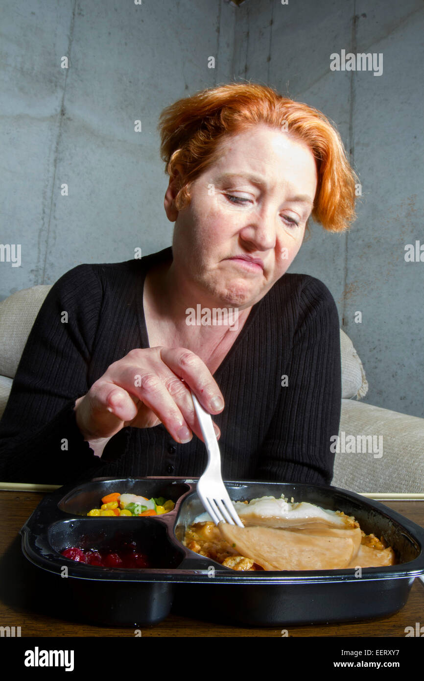 Unhappy woman eating a TV dinner - Stock Image