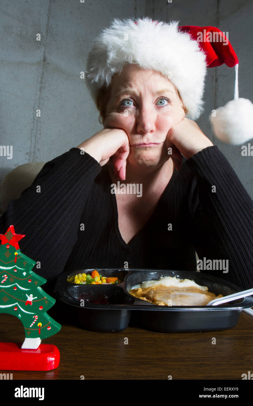Unhappy woman wearing a christmas stocking hat eating a turkey TV dinner on a tray table in the basement - Stock Image
