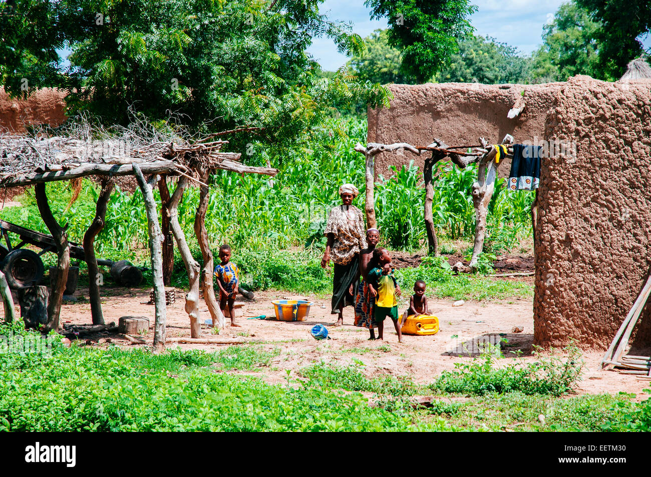 Woman and children in their mud brick huts village, Mali. - Stock Image